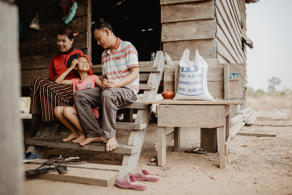 Cambodian family outside their house on wooden beams. Girl sits in lap of father and mother