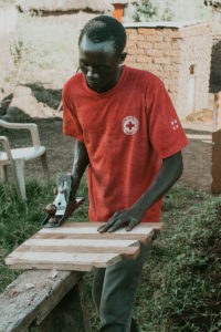 Peter works on a piece of furniture at his carpentry shop in Uganda.