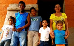 Nicaraguan farmer stands outside an orange house with his wife and four kids.
