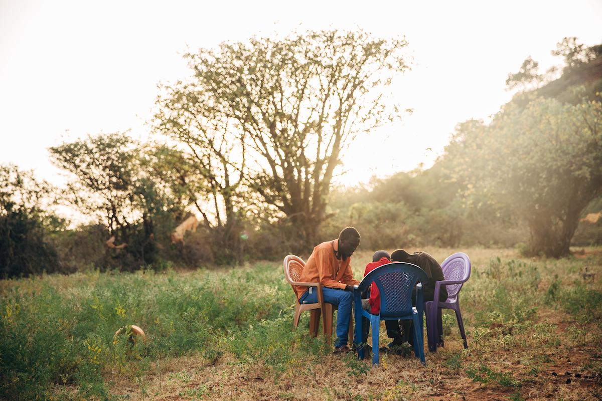 Men in Kenya pray together