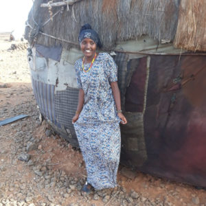Kenyan girl stands outside her hut, smiling after receiving menstrual hygiene products.