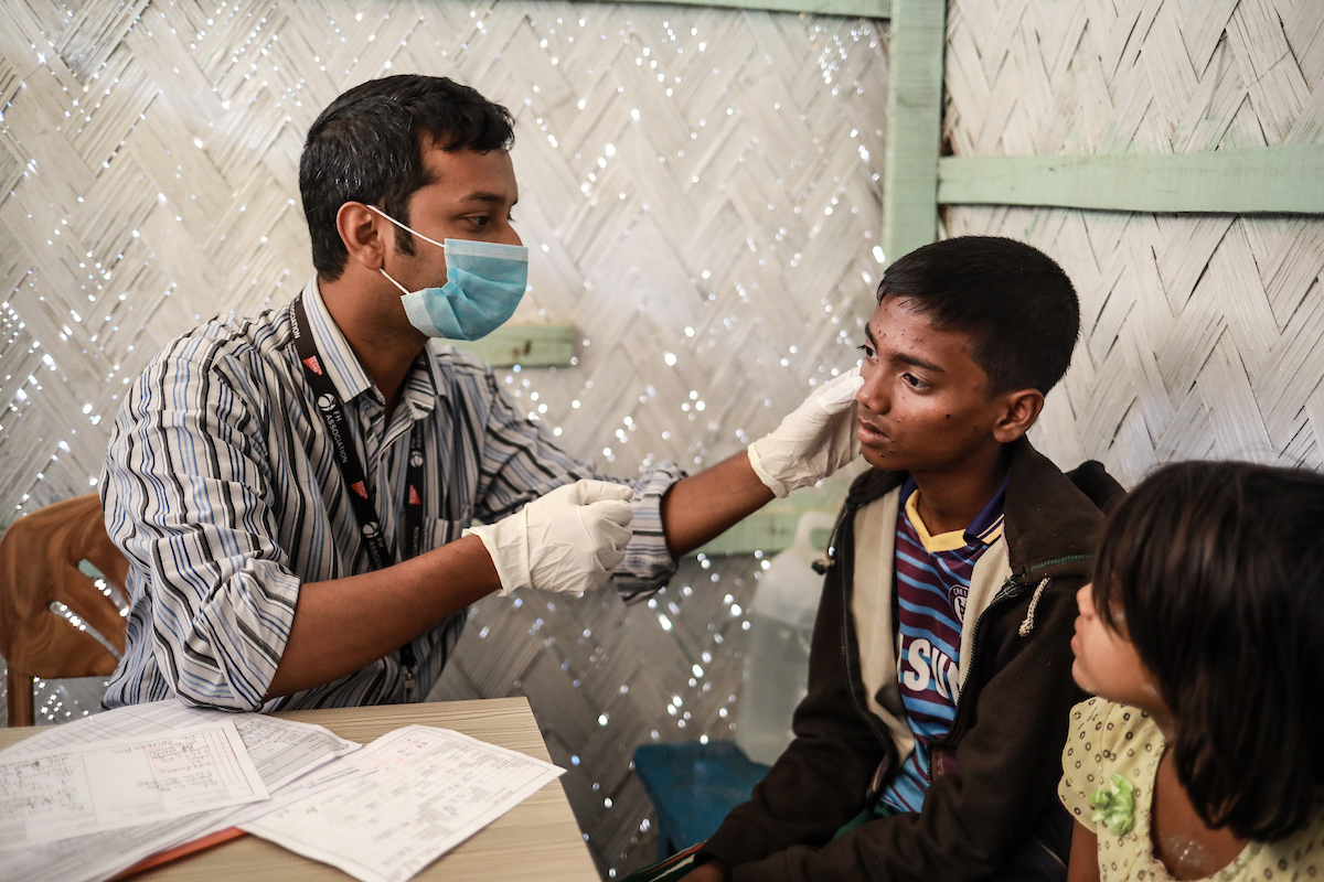 Community health worker in face mask examines a young boy in Rohingya refugee camp, where FH is working to prevent coronavirus in Cox's Bazar