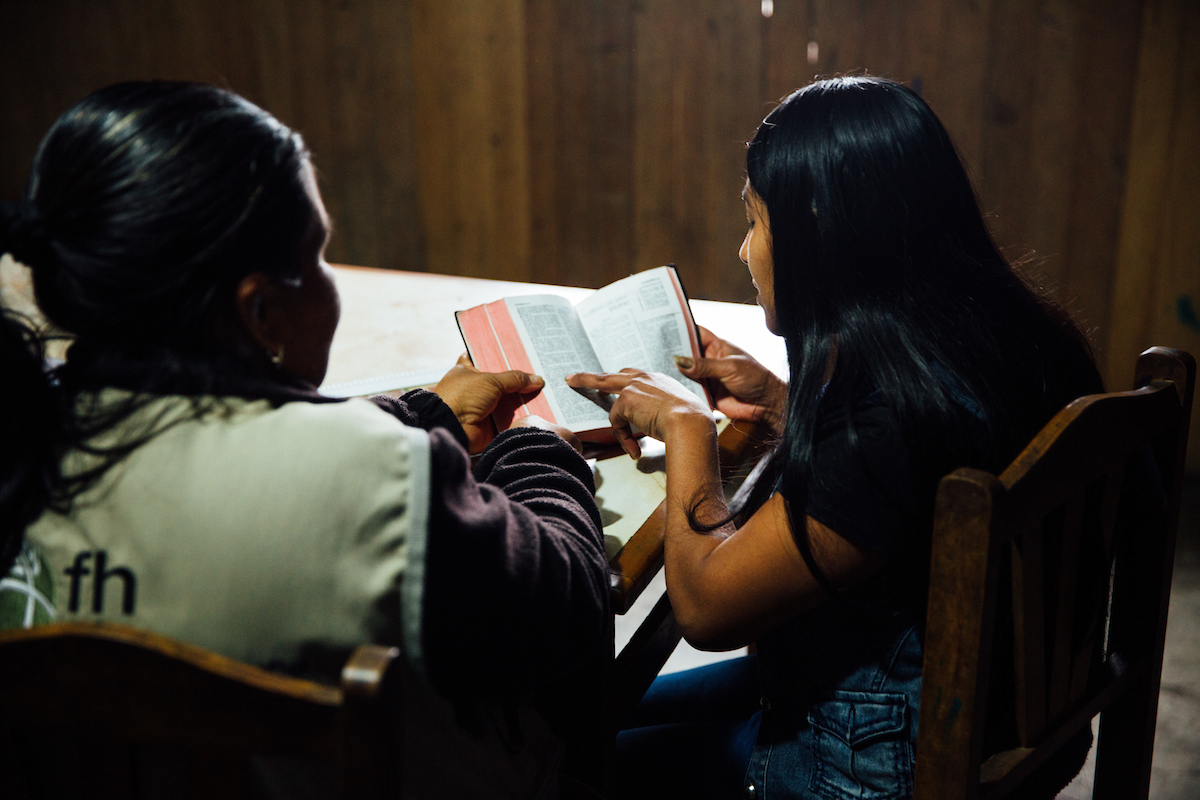 FH staff member and young Peruvian girl read the Bible together.