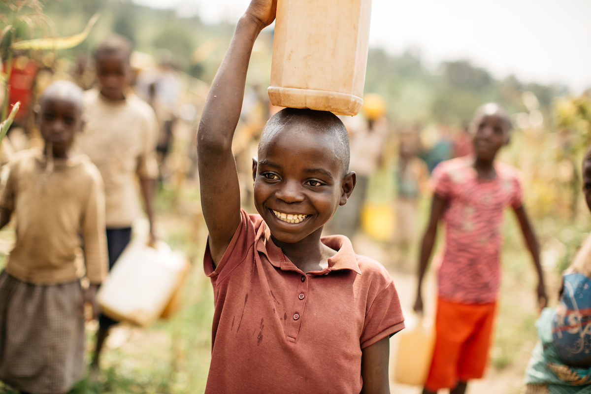 Boy carrying yellow water jug