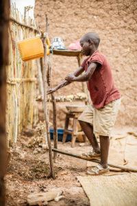 Burundian boy washing hands with tippy tap