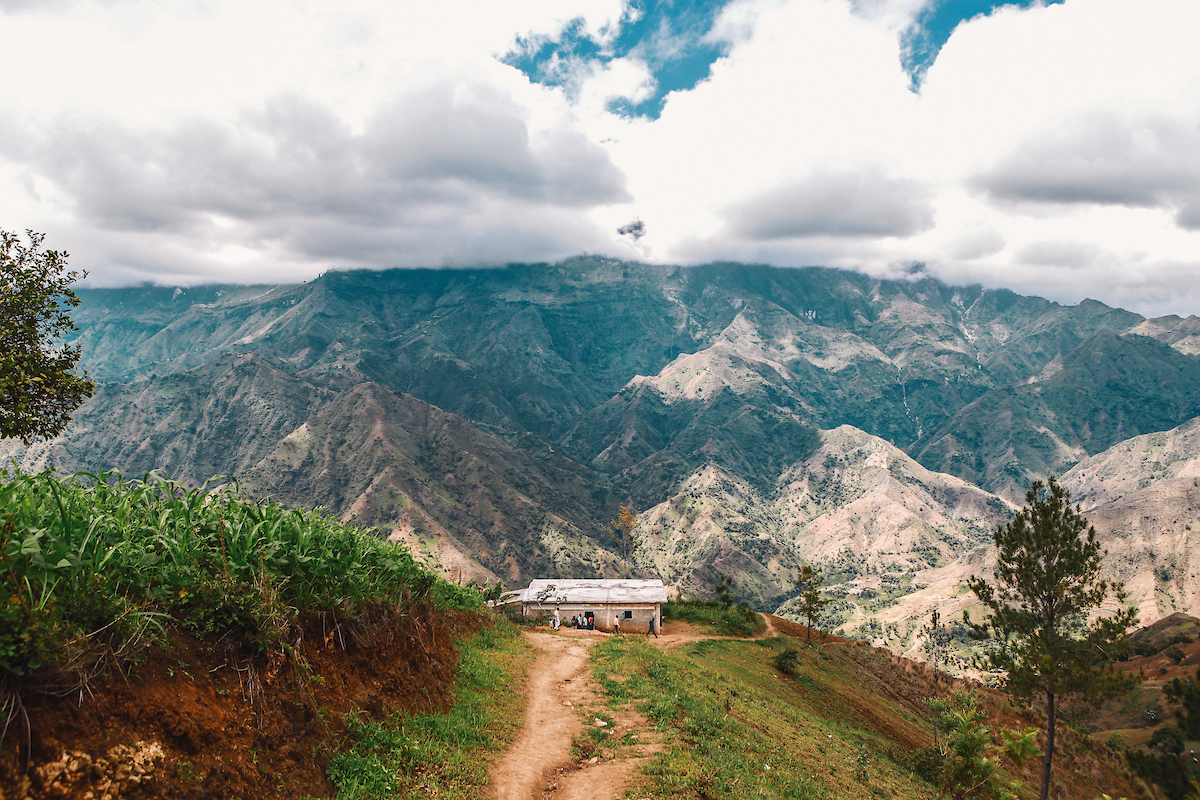 Small house with metal roof set against mountains and beautiful Haiti landscape