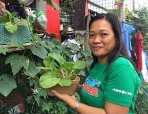 woman in green shirt showing off vegetable garden