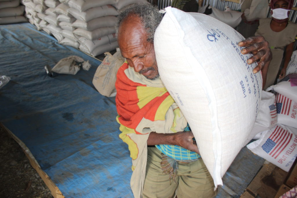 A beneficiary receiving his ration of food
