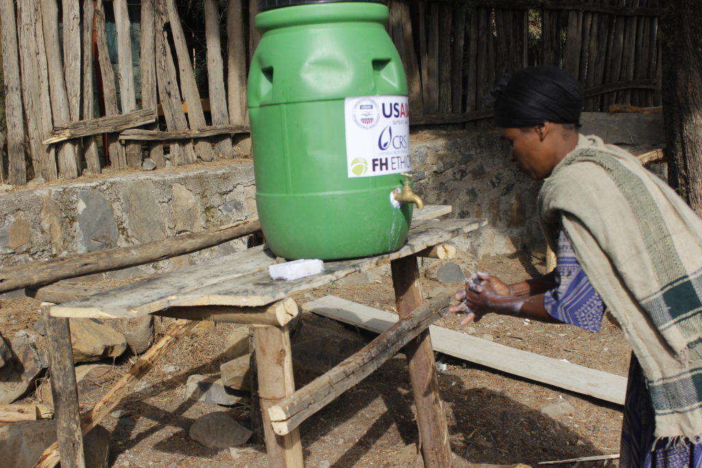 a woman washing her hands at a handwashing station