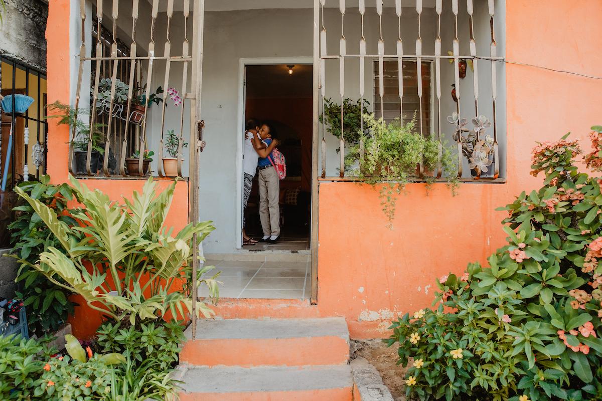 Mère embrasse sa fille avec un sac à dos pour aller à l'école en République dominicaine, montrant l'extérieur orange de la maison