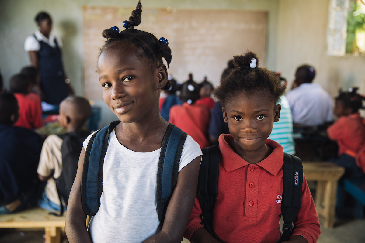 Two girls elementary school aged wearing white and red shirts inside Haitian classroom