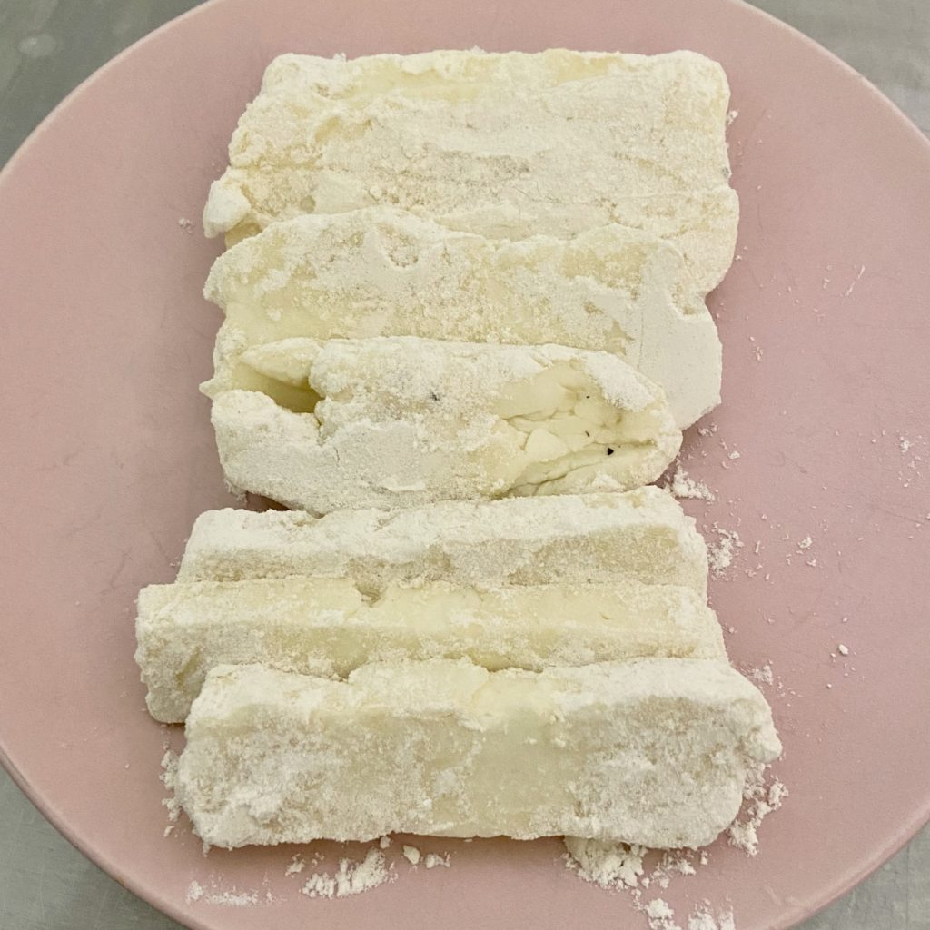 frying cheese covered in flour on a plate