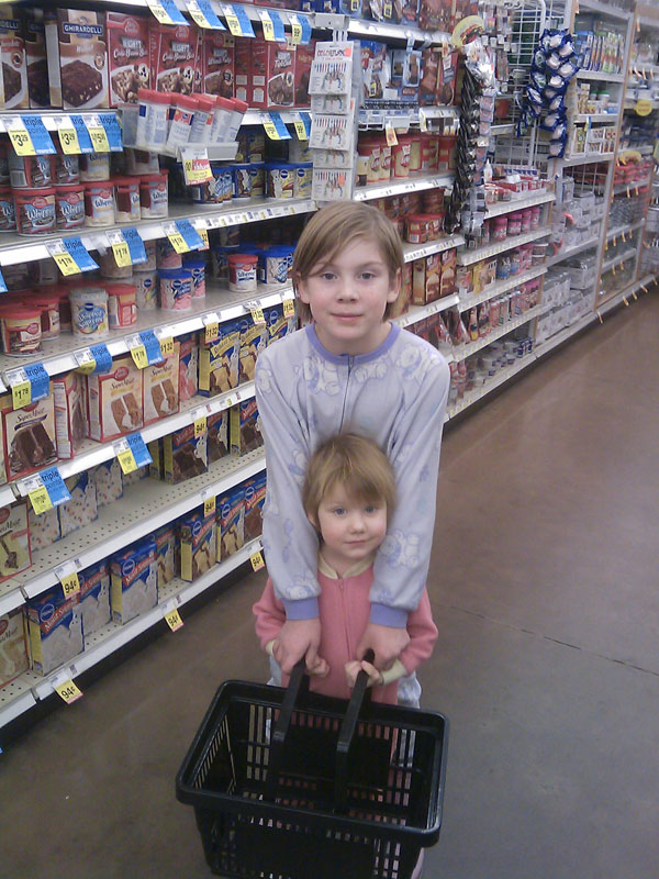 Buying chocolate in the store with my two pajama/moon-boot wearing kids