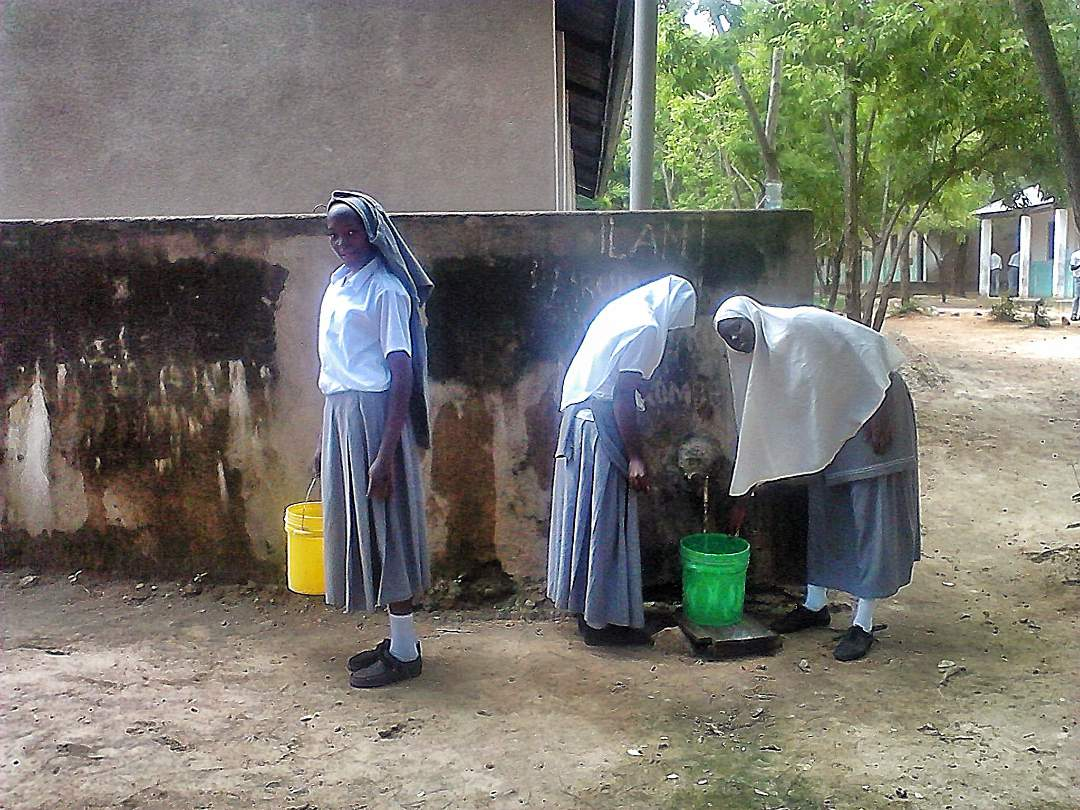 Female students filling water buckets