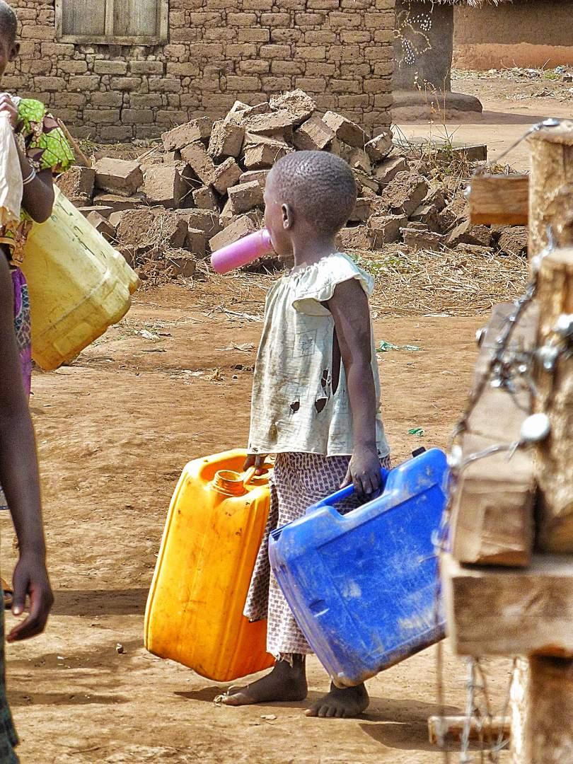 Young boy carrying water jugs