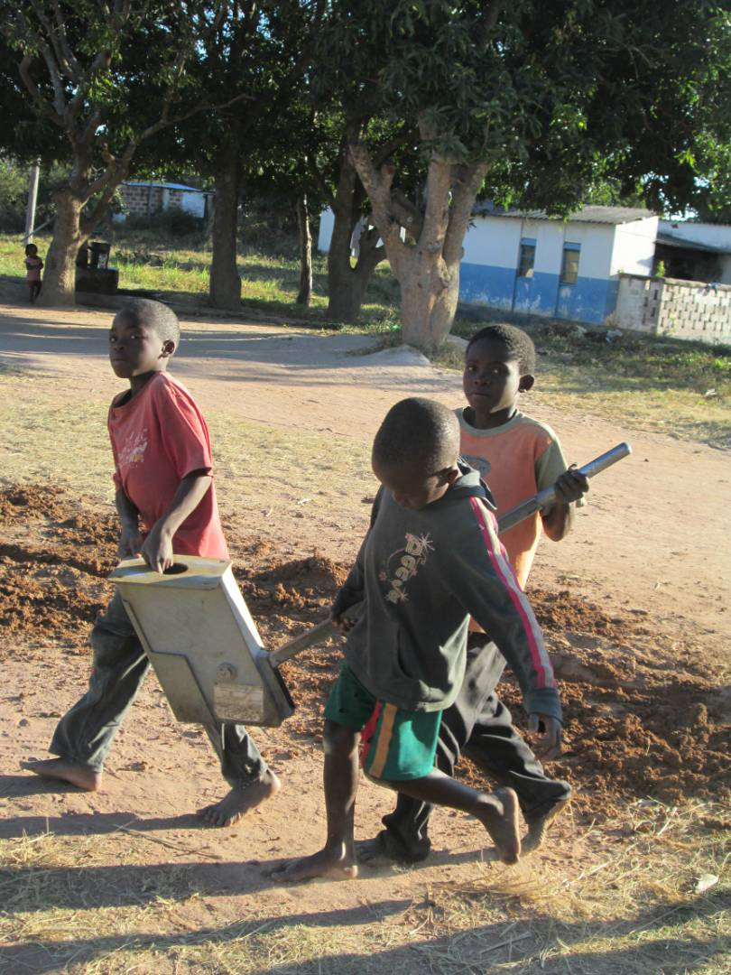 Children helping to remove old system at Mabumba