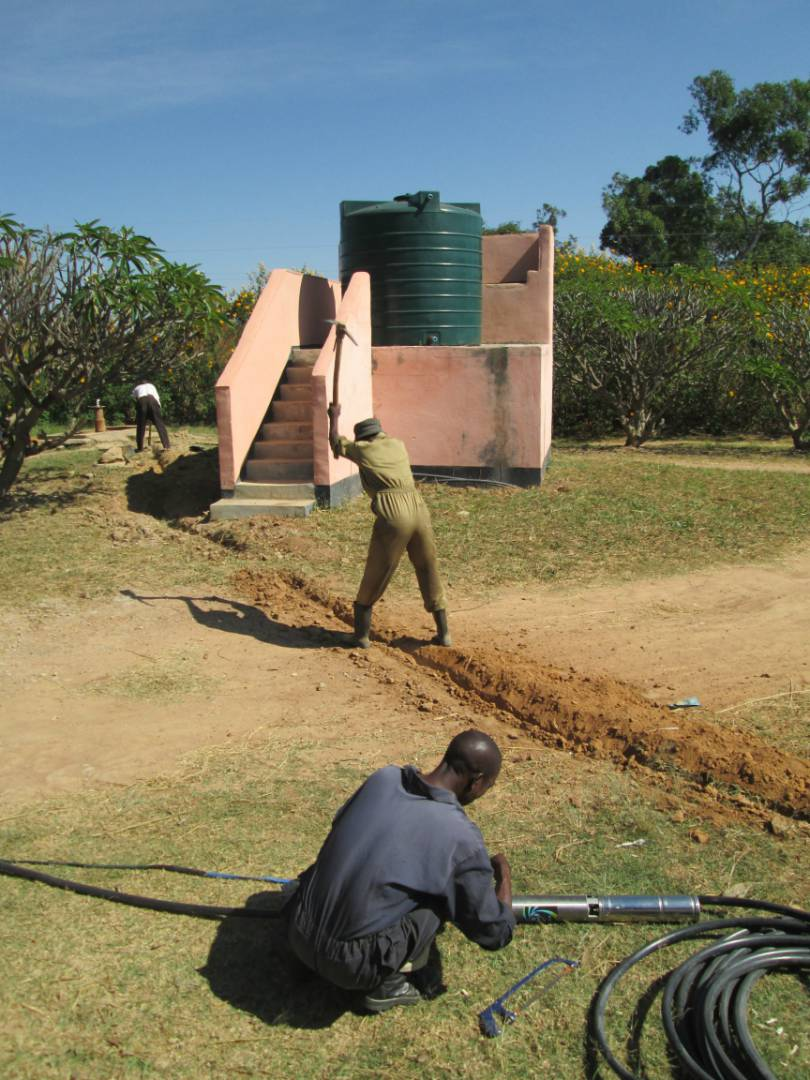 Preparing the pump and digging the trench for piping at Mantumbusa