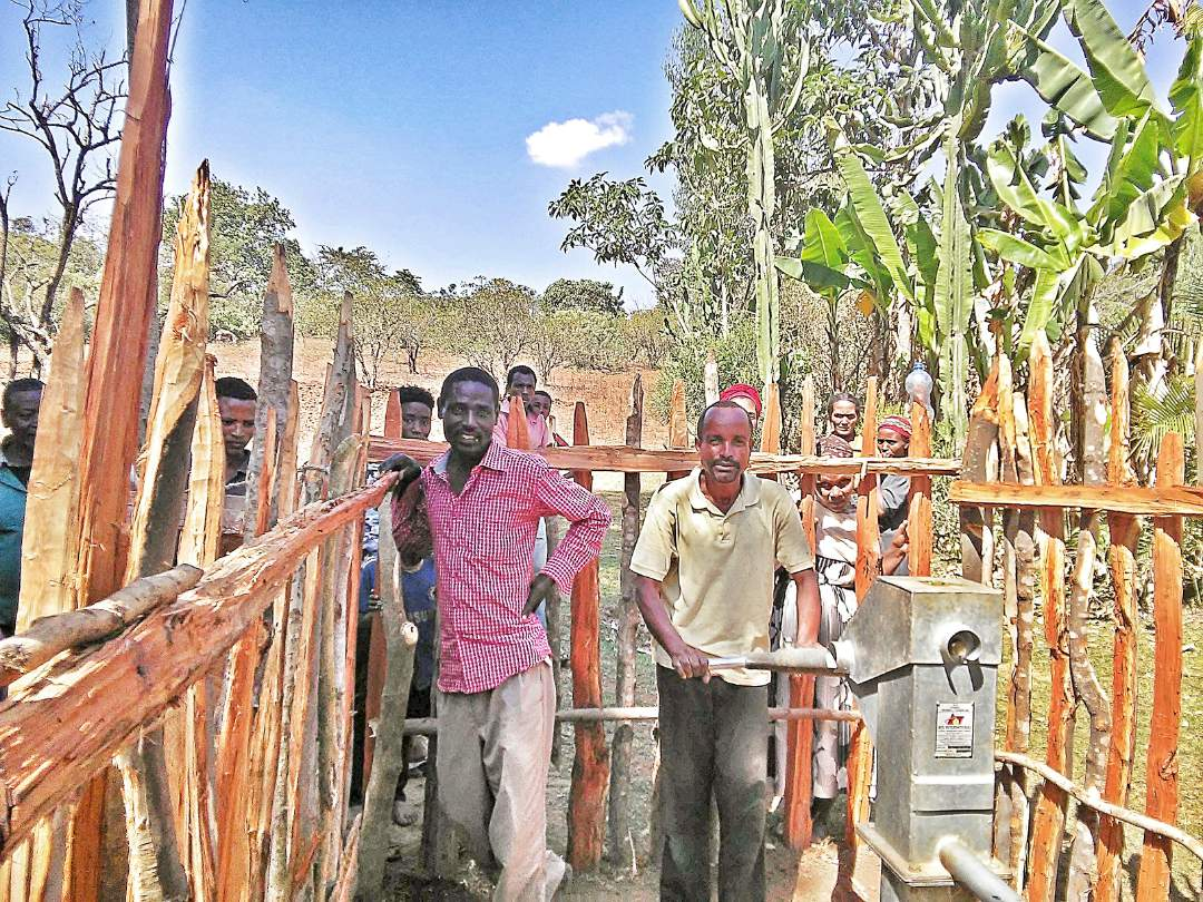 Village men utilizing the well