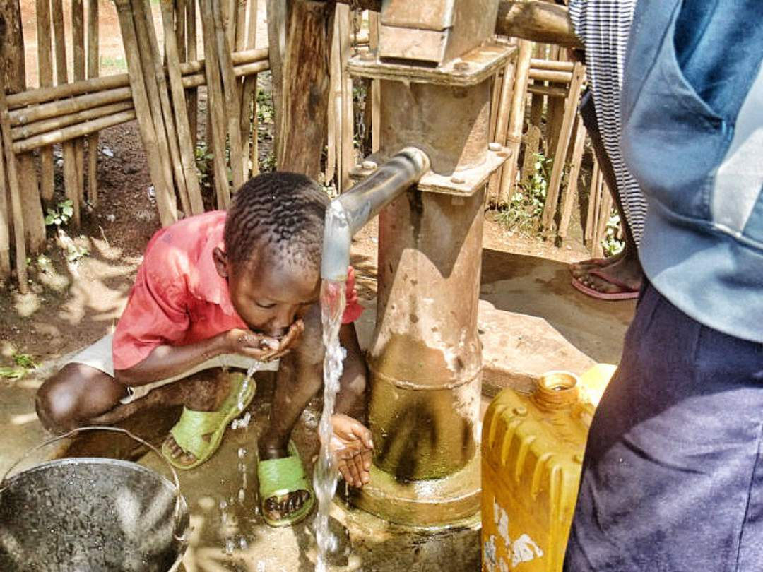 boy getting water from the well